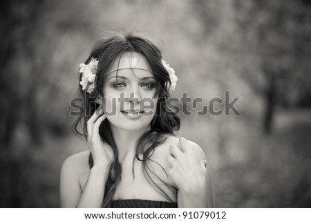Black-and-white hortrait of beautiful young woman with daisies in her hairoutdoors, park, European, White, Caucasian - stock photo