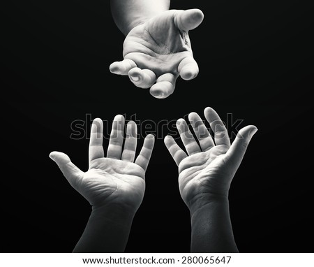Black and white human hands or Adam's hand reaching to hand of God over black background. - stock photo