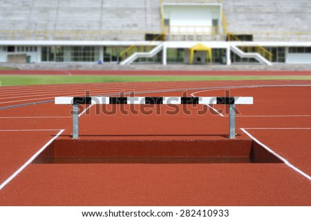 Black and white hurdles over water in track field - stock photo