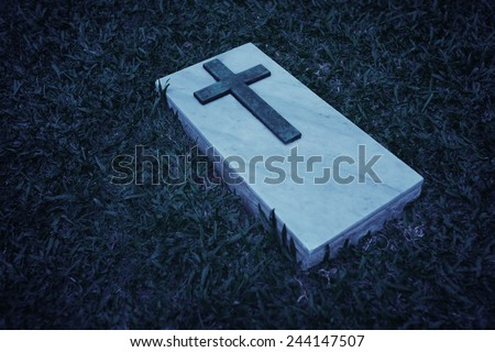Black and white image of a cross on a marble slab, marking a grave at this cemetery in Singapore - stock photo