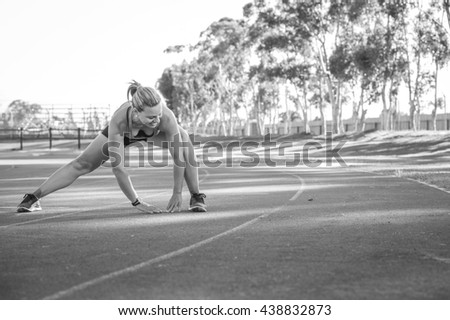 Black and white image of a Fit and happy female athlete doing stretches before she starts training on a tartan athletics track - stock photo