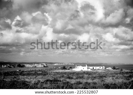 Black and white image of a house near the sea in Sagres, in the Algarve of Portugal, Europe, with cliffs in the background and dramatic clouds in the sky - stock photo