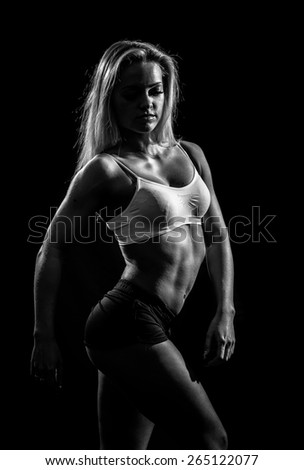 Black and white image of a muscular female against black background. - stock photo