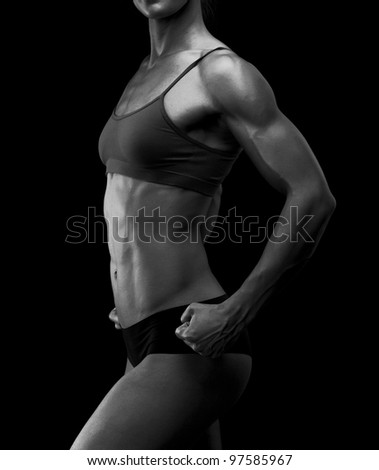 Black and white image of a muscular female body against black background. - stock photo