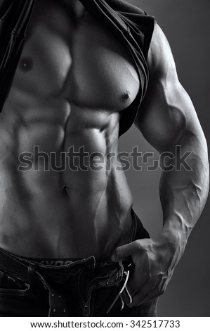 black and white image of a muscular male torso  - stock photo