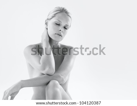 Black and white image of a naked woman holding her neck in pain, with her eyes closed. - stock photo