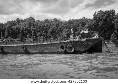 Black and white image of a rusty disused barge on the River. - stock photo