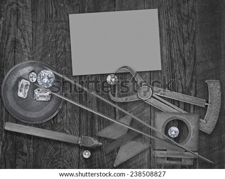 black and white image of a vintage jeweler tools and diamonds over wooden bench, blank card for your business - stock photo