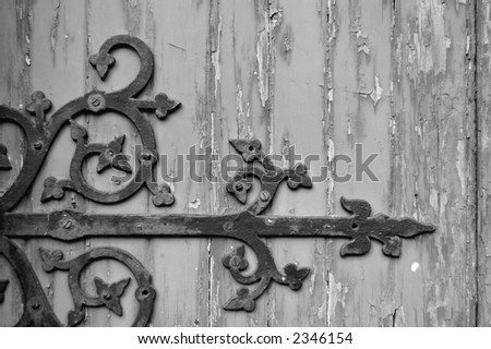 Black and white image of a weathered church door with a wrought iron decoration - stock photo