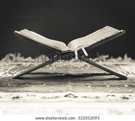 Black and white image of an old Holy Book. Closeup Koran with beautiful light from window of mosque. Eid Mawlid An Nabi, Milad Un Nabi, Prophet's Birthday, Muhammad, Muhammed, Mohammad concept. - stock photo
