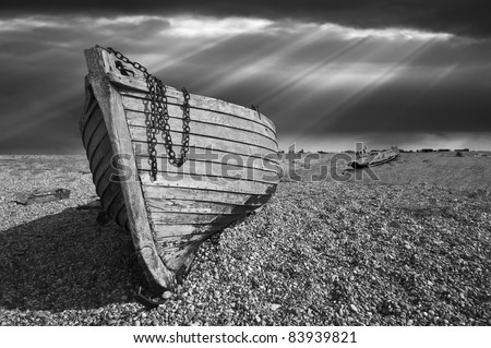 black and white image of an old wooden fishing boat left to rot and decay on the shingle beach at Dungeness, England, UK. - stock photo