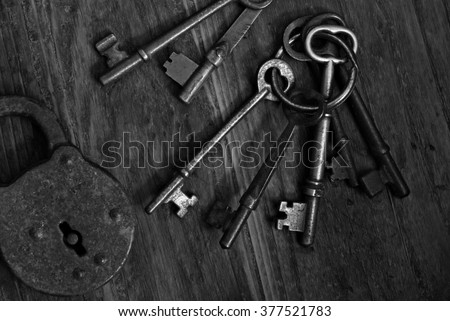 Black and white image of antique skeleton keys and padlock on dark, rustic wood background.  Low key still-life with natural, directional lighting for effect. - stock photo