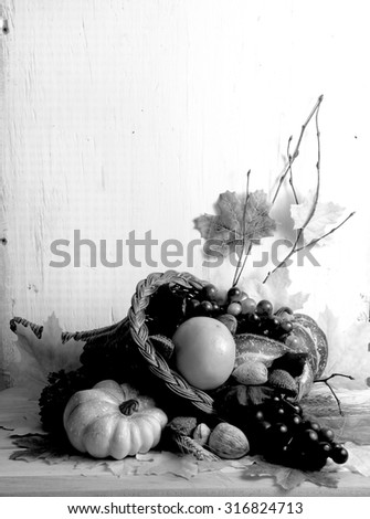 Black and white image of fall cornucopia containing fruits and vegetables and nuts with autumn leaves scattered around with rustic wood background. Vertical composition with copy space in upper left. - stock photo