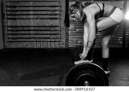 Black and white image of Fit woman working out at a gym. - stock photo