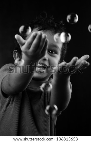 Black and white image of girl playing with bubbles - stock photo