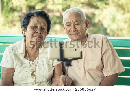 Black and white image of Happy senior couple posing for a selfie at home - stock photo