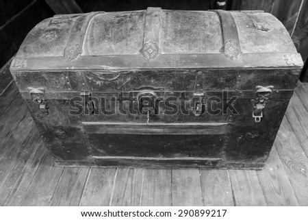 Black and White Image of Old Dusty Antique Treasure Chest with Rusty Iron Accents and Key in Lock on Deck of Sailing Ship - stock photo