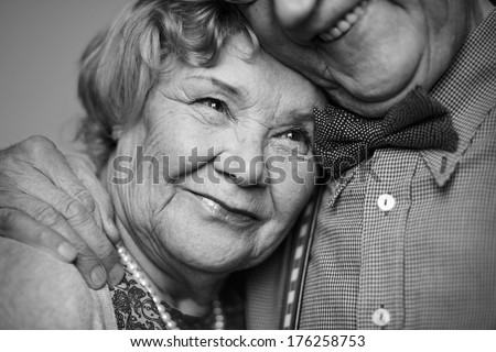 Black-and-white image of senior female being embraced by her husband - stock photo