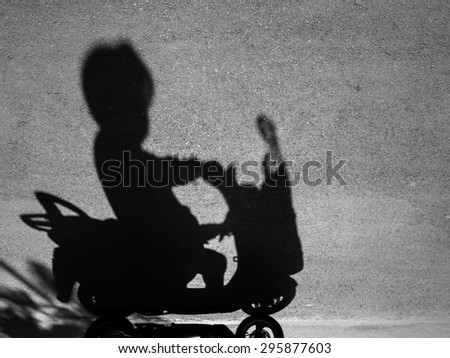 Black and white image of shadow of a man riding  motorcycle. - stock photo