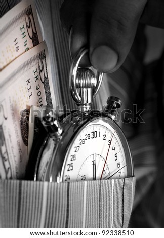 Black and white image of stopwatch with banknotes into the pocket of  man shirt - stock photo