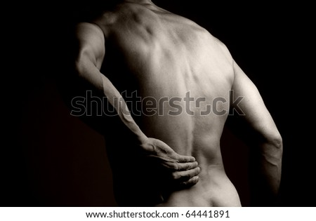 Black and white image of the back of a muscular man. He is rubbing his lower back as if to indicate a backache. - stock photo
