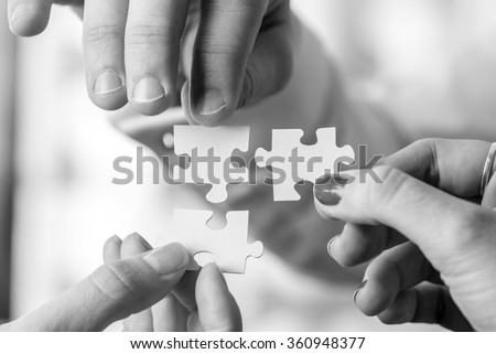 Black and white image of three people, male and female, holding puzzle pieces to match them. Conceptual of teamwork, cooperation and problem solving. - stock photo