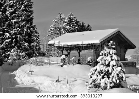 Black and white image of traditional alpine huts in a snowy, wintery setting in the Swiss Alps. - stock photo