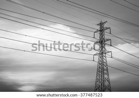 Black and white image.Silhouette of high voltage electrical pole. Sky background.  - stock photo