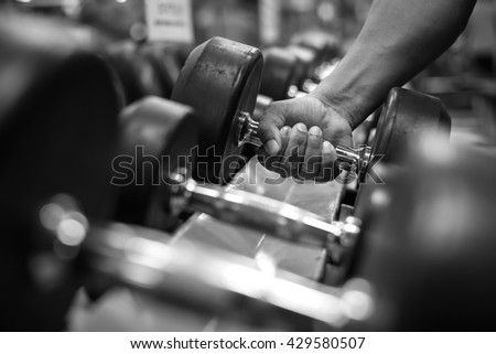 Black and white images Hand holding dumbbell in the gym bodybuilding. - stock photo