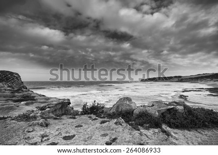 Black and white landscape of ocean rocks and clouds in artistic conversion - stock photo