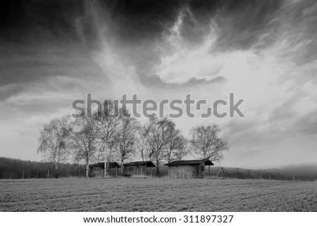 black and white landscape with several barns in agricultural farmland  - stock photo