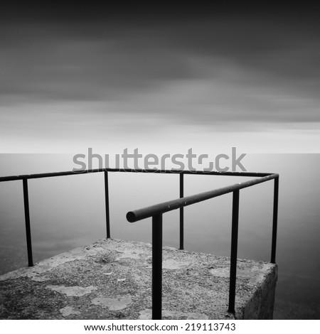 Black and white long exposure shot of pier with beautiful sky. Odessa, Ukraine - stock photo