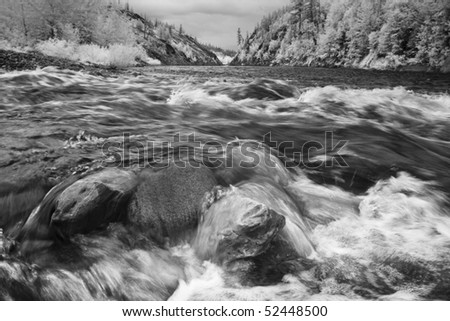 Black-and-white low angle view of river water rushing over rocks, with the tree-covered hills of Glacier National Park visible in the background. Horizontal shot. - stock photo