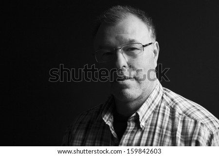 Black and white low-key portrait of middle-aged man - stock photo