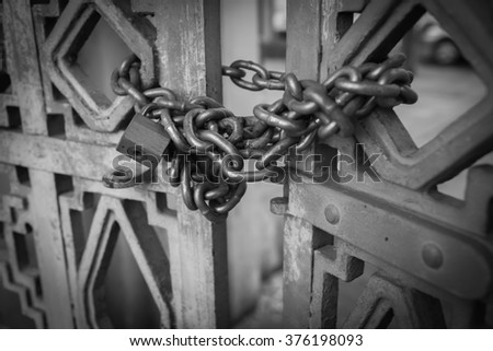 black and white metal padlock and chain on metal gate - stock photo