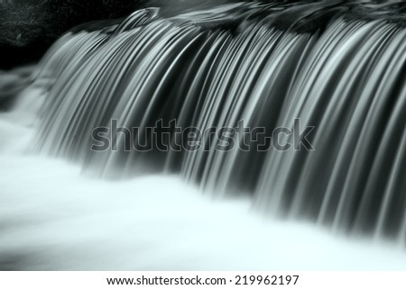 Black and white Mountain river background with small waterfalls in tropical forest. - stock photo