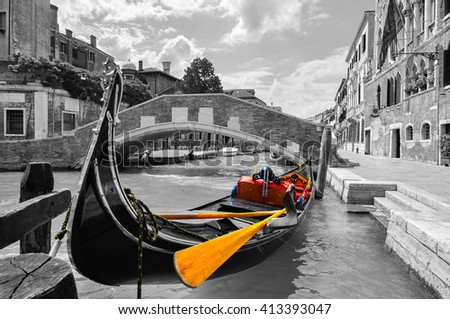 Black and white of a beautiful canal in Venice with selective color on the gondola - stock photo