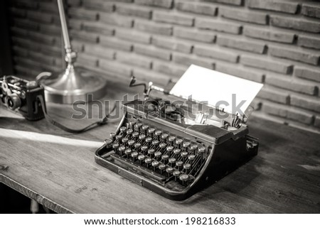 Black and white of an old typewriter with paper on a wooden table, photo in retro style - stock photo