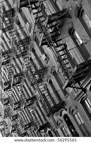 black and white of metal fire escapes outside buildings in Manhattan, New York - stock photo
