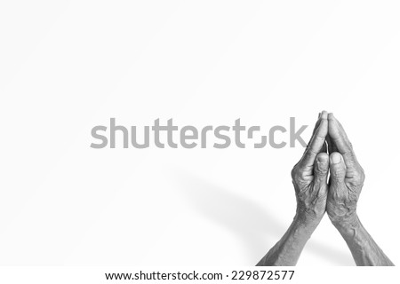Black and white old mothers hands praying or pay obeisance over white background. - stock photo