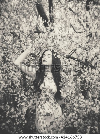 Black and white outdoors fashion photo of beautiful young lady in the garden of cherry blossoms - stock photo