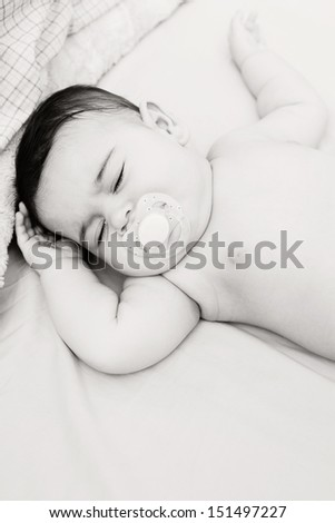 Black and white over head close up portrait of a baby girl sleeping on a bed at home and sucking a white dummy, dreaming. - stock photo