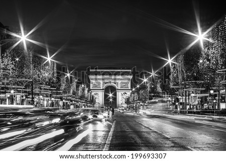 Black and White Paris: Evening traffic on Champs-Elysees in front of Arc de Triomphe (Paris, France) at Christmas Time - stock photo