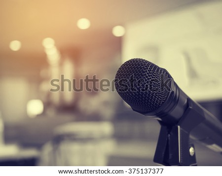 Black and white photo and lighting of the black microphone in concert hall or conference room with defocused bokeh lights in background. Extremely shallow dof. : Vintage style and filtered process. - stock photo
