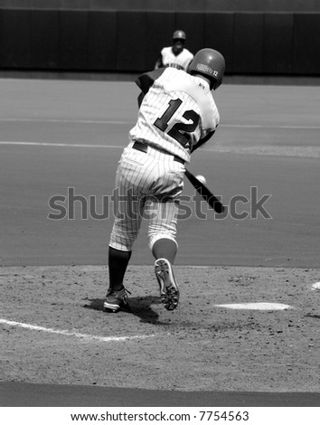 Black and white photo of a batter hitting the ball - stock photo