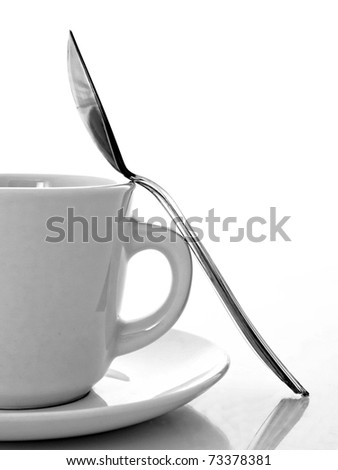 Black and white photo of a cup,saucer and spoon. - stock photo