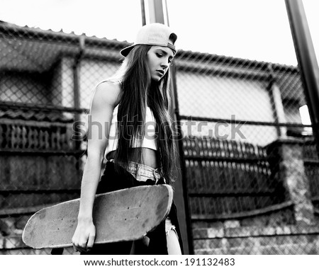 Black and white photo of a girl with skateboard against the sun - stock photo