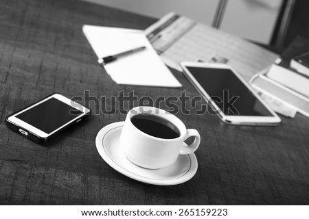 Black and white photo of a no name coffee cup and a stack of books in background on a wood table with shallow depth of field - stock photo