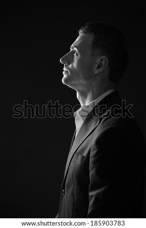 Black and white photo of a pensive man looking up - stock photo