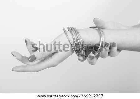 Black and white photo of a woman with nice nails showing jewel on her arm with her hands on a light gray background - stock photo